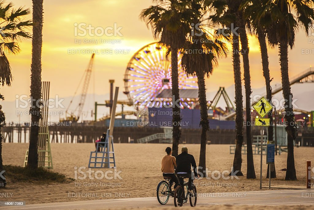 People cycling on Santa Monica Beach at sunset stock photo