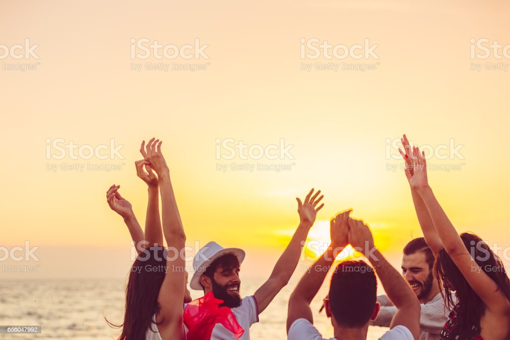 people dancing at the beach with hands up. concept about party, music and people stock photo