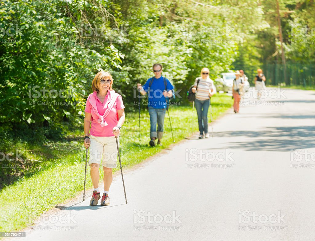 People doing nordic walking in a park stock photo