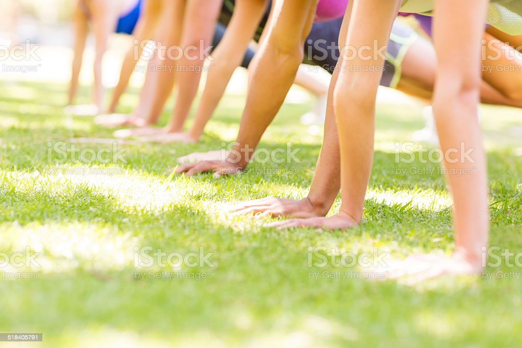 People Doing Push-Ups In Park At Bootcamp Class stock photo