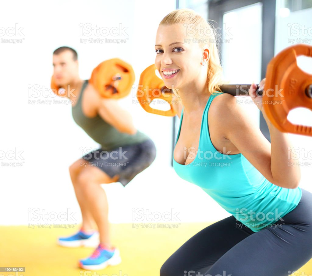 People doing squats in a gym stock photo