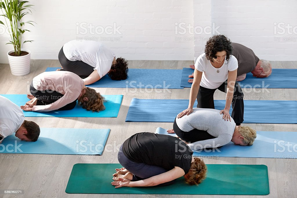 People doing yoga with instructor at health club stock photo