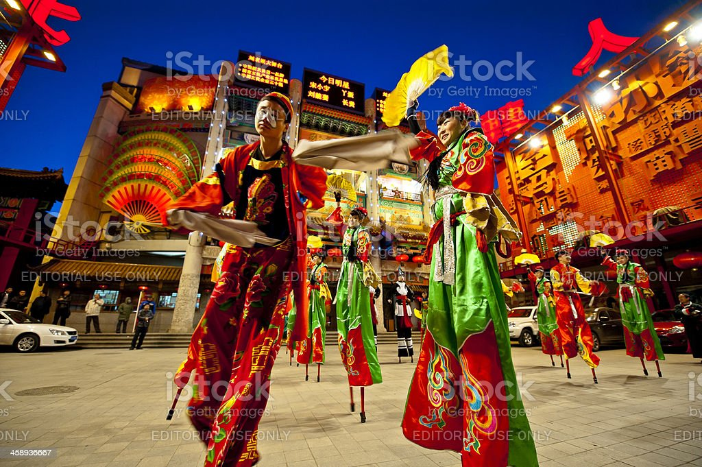 People dress in traditional Chinese style walk on stilts stock photo