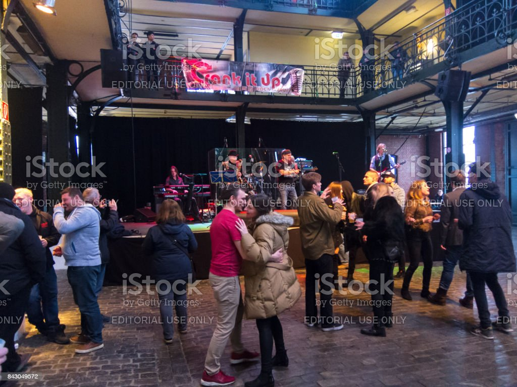 People drink and dance in the indoor fish market in Hamburg. stock photo