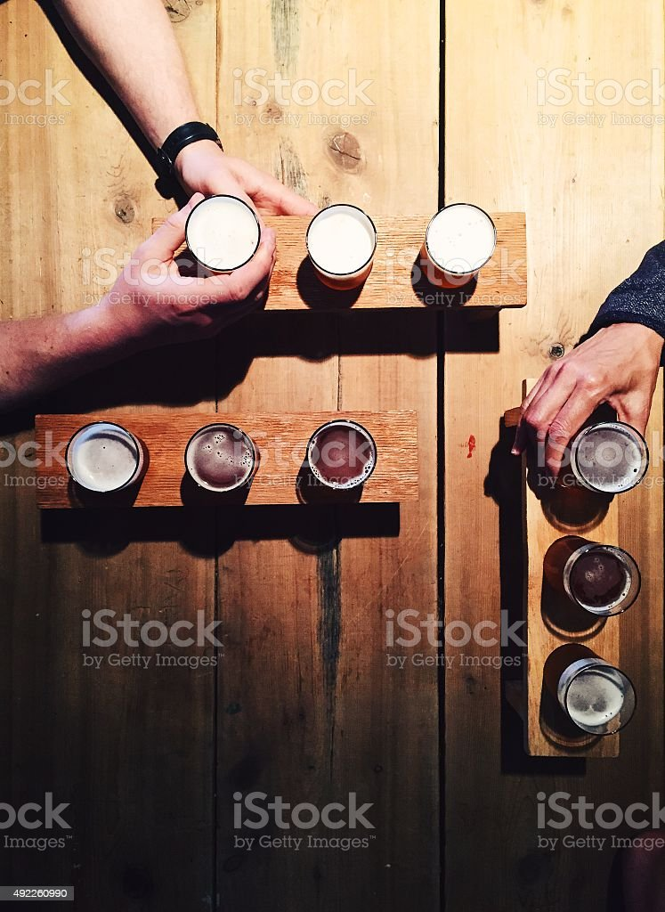 People drinking local beer from tasting palettes at craft brewery stock photo