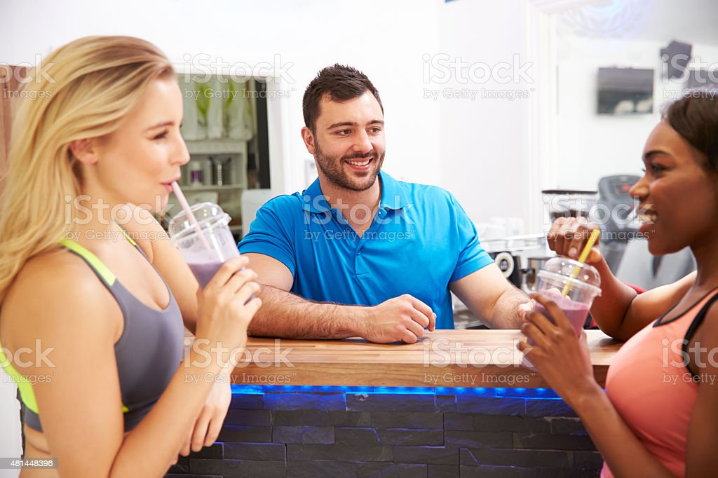 People drinking protein shakes at the fitness bar in gym stock photo