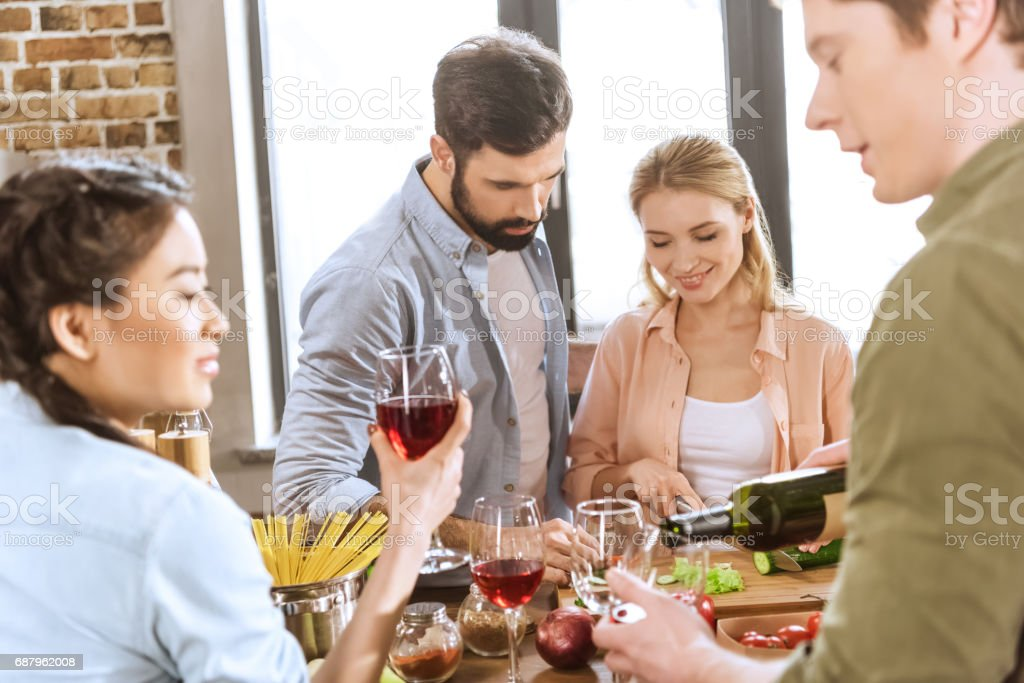 people drinking wine at home party stock photo