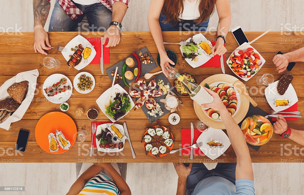 People eat meals drink alcohol at festive table dinner party stock photo