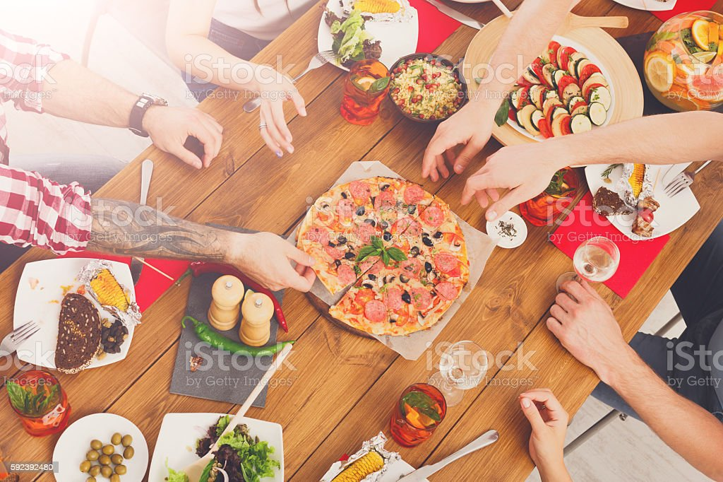 People eat pizza at festive table dinner party stock photo