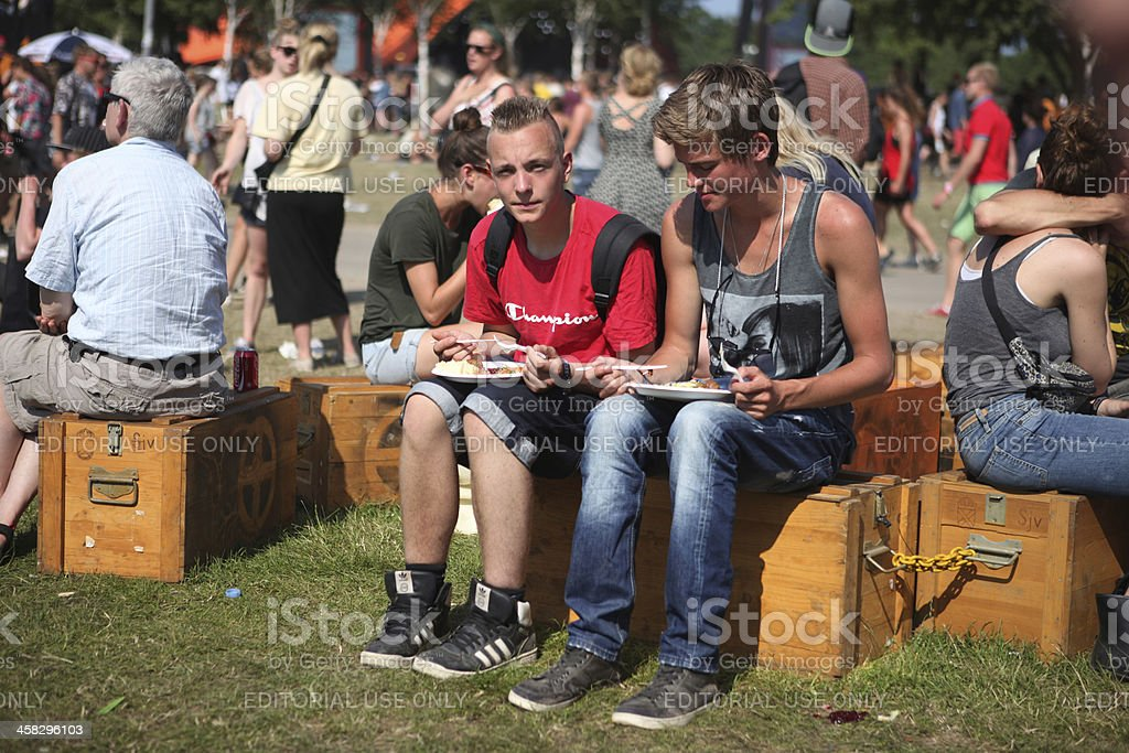 People eating and resting during Roskilde Music-Festival in Denmark stock photo