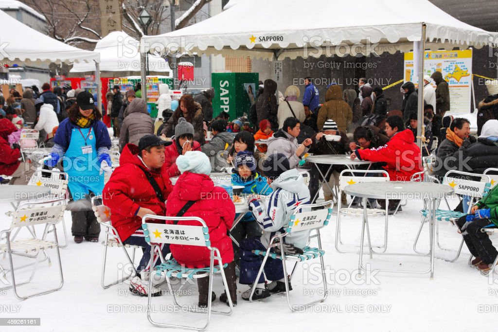 People eating during the Sapporo Snow Festival royalty-free stock photo
