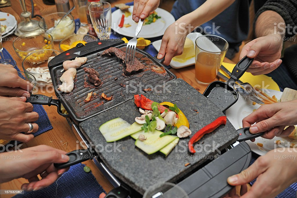 people eating raclette - grill and hands stock photo