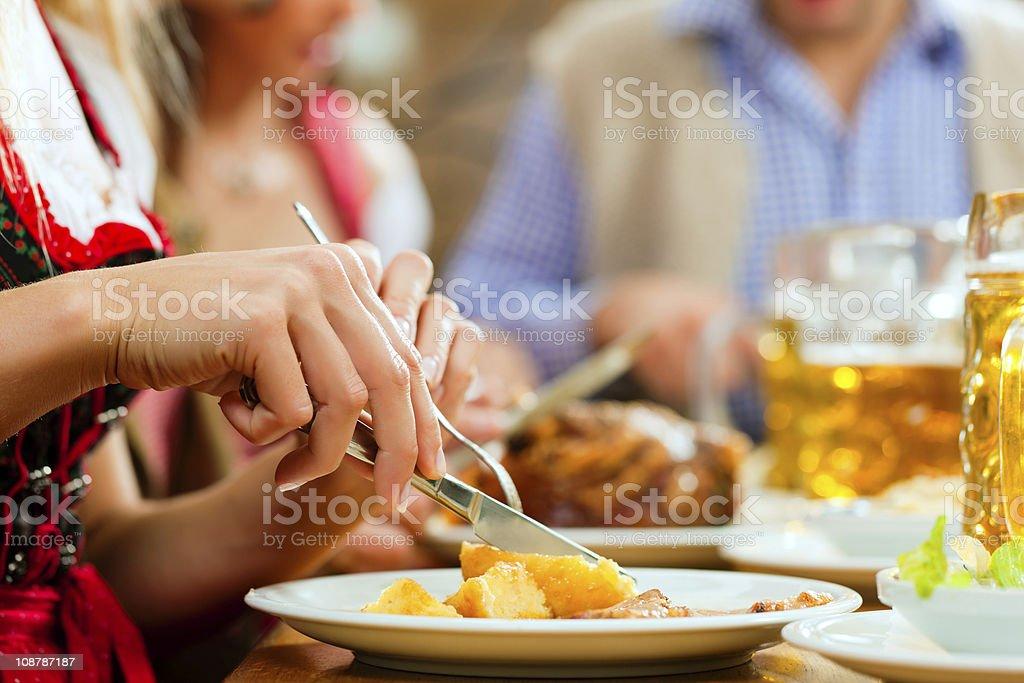 People eating roast pork in Bavarian restaurant stock photo