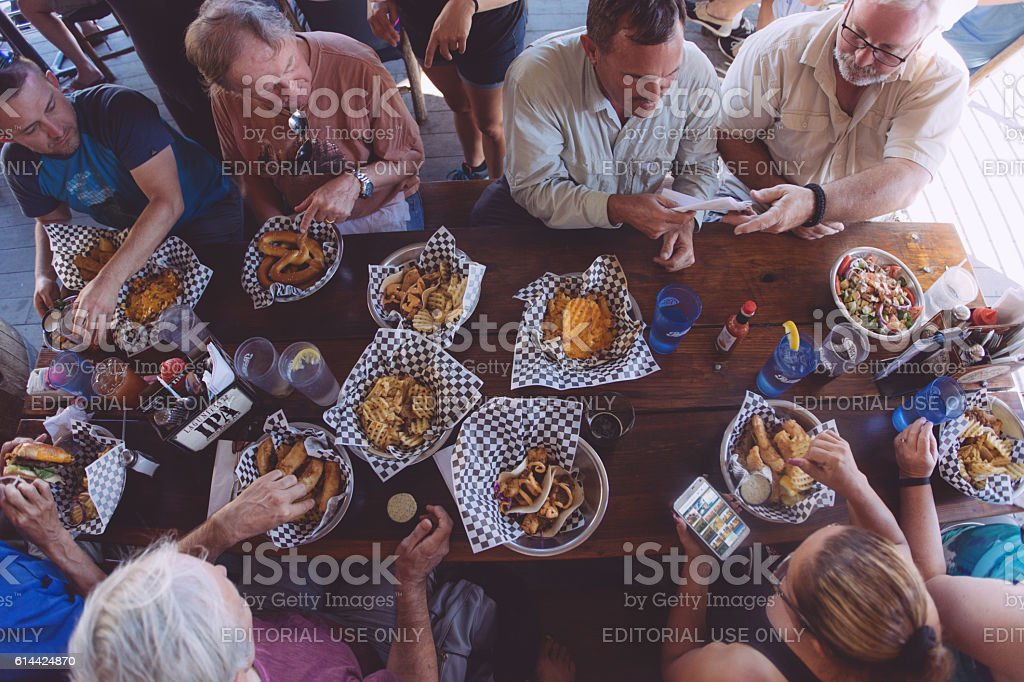 People eating rustic fast food: Fish Taco, Fish and Chips stock photo