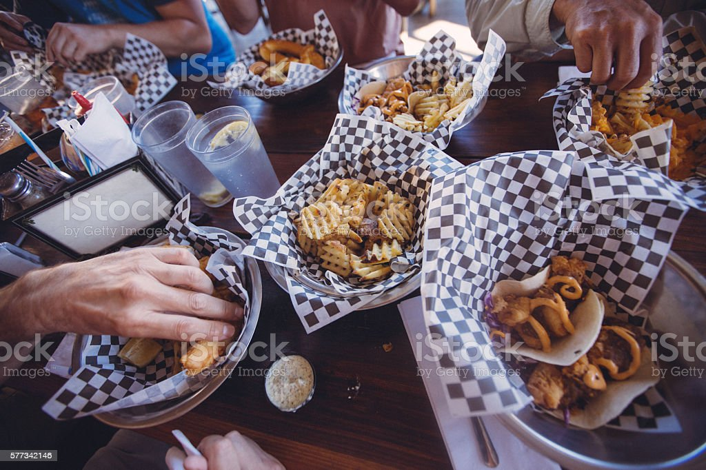 People eating simple fast food: Fish Taco, Fish and Chips stock photo
