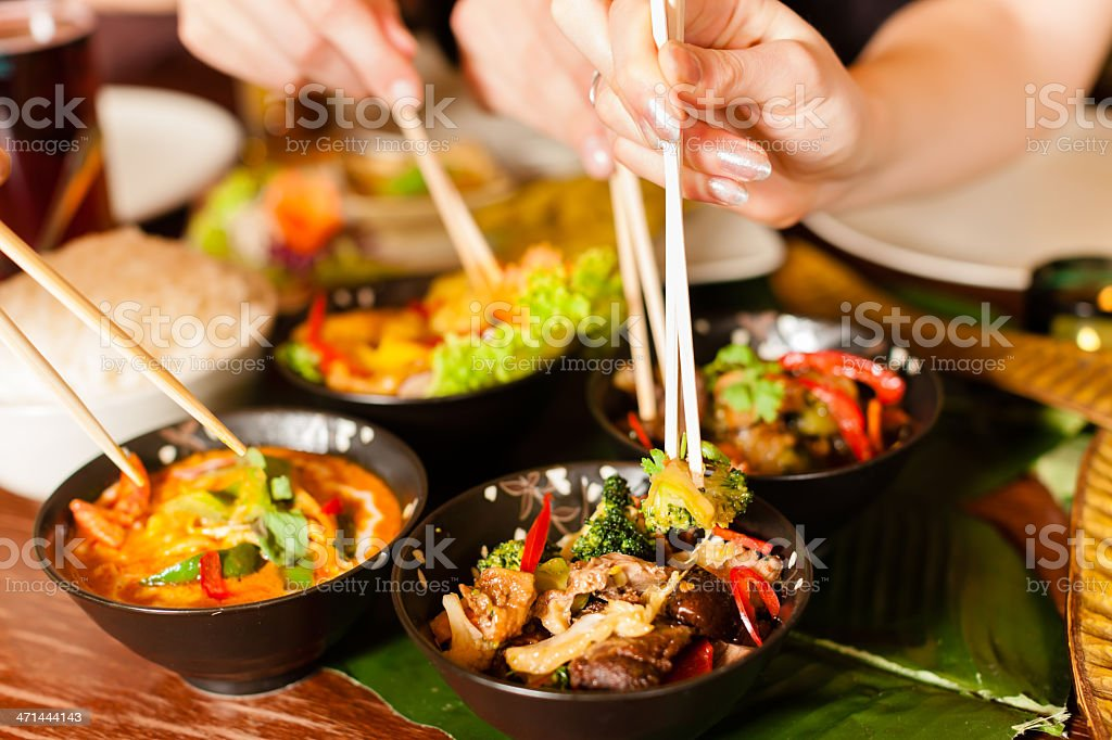 People eating Thai food with chopsticks stock photo