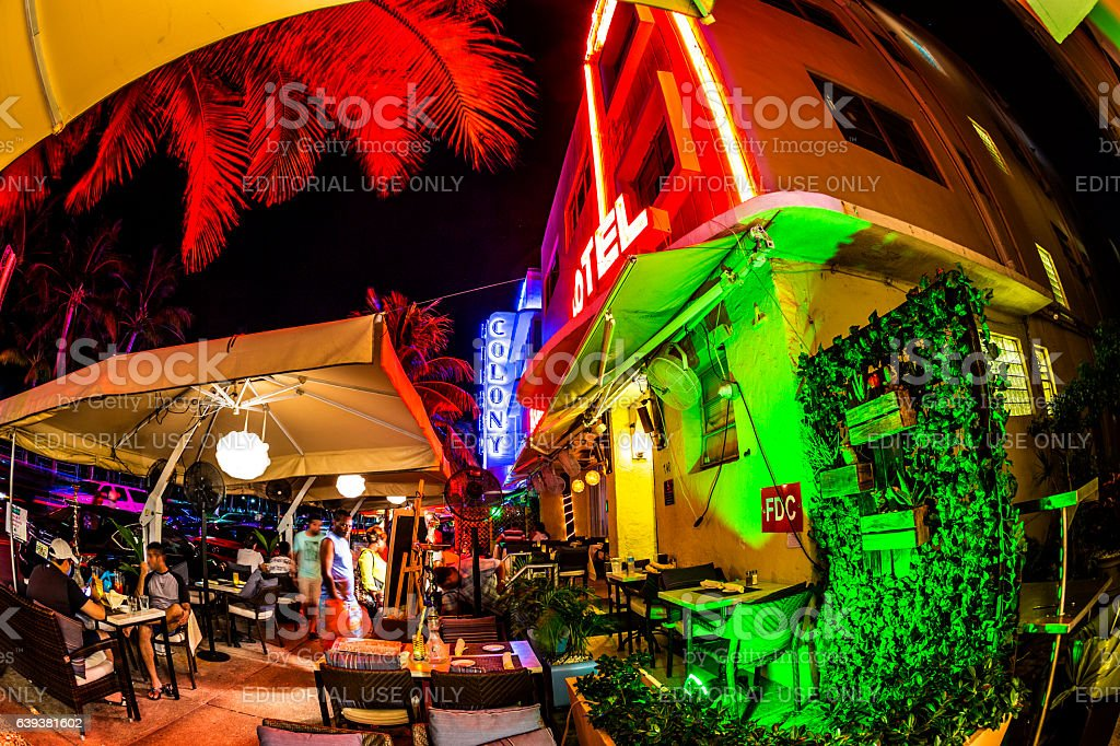 people enjoy the bar and restaurant at night at Ocean drive in South...