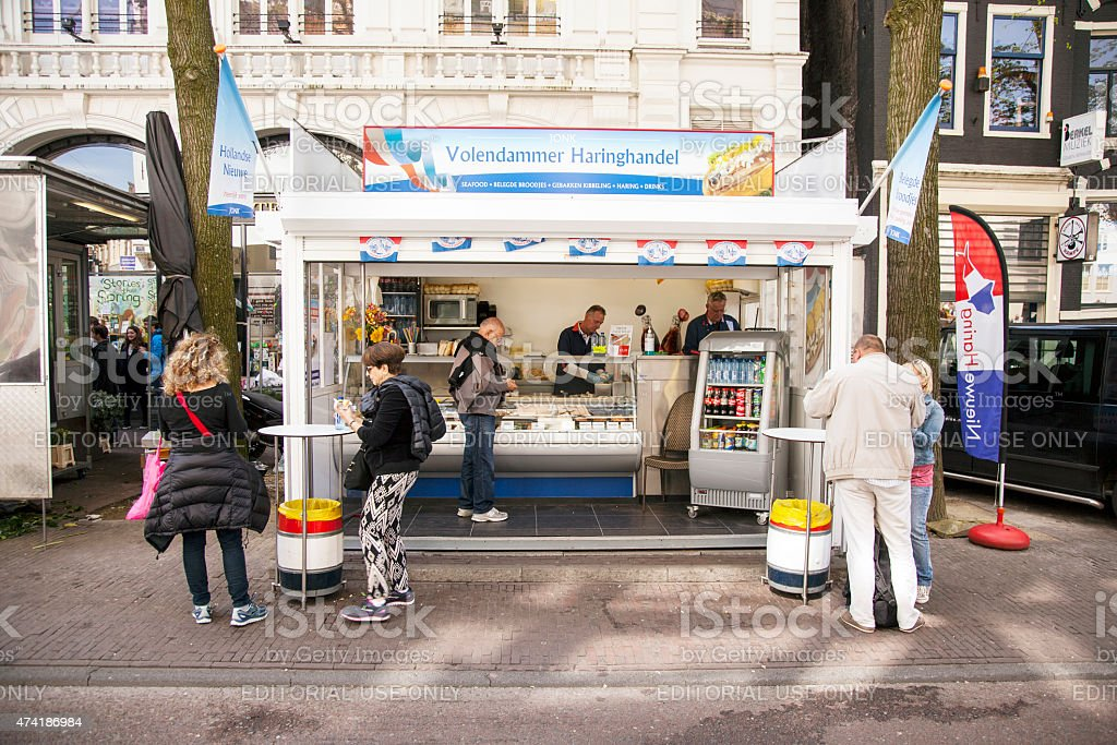 people enjoy fresh herring at stall in centre of amsterdam stock photo