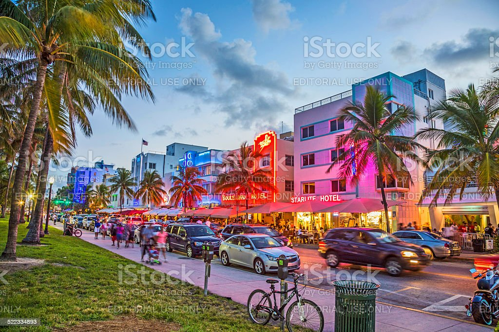 people enjoy palms and art deco hotels at Ocean Drive stock photo