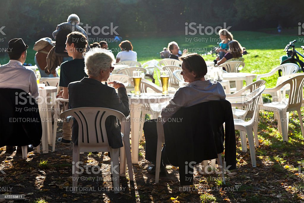 people enjoy the last warm day in the park stock photo