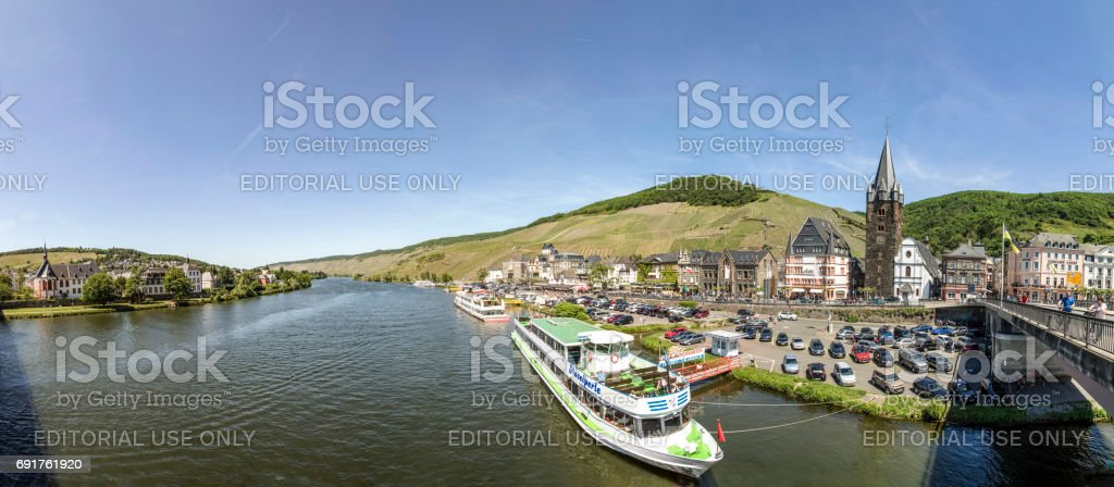 people enjoy the river cruise on river Moselle with view to old historic town of Bernkastel-Kues stock photo