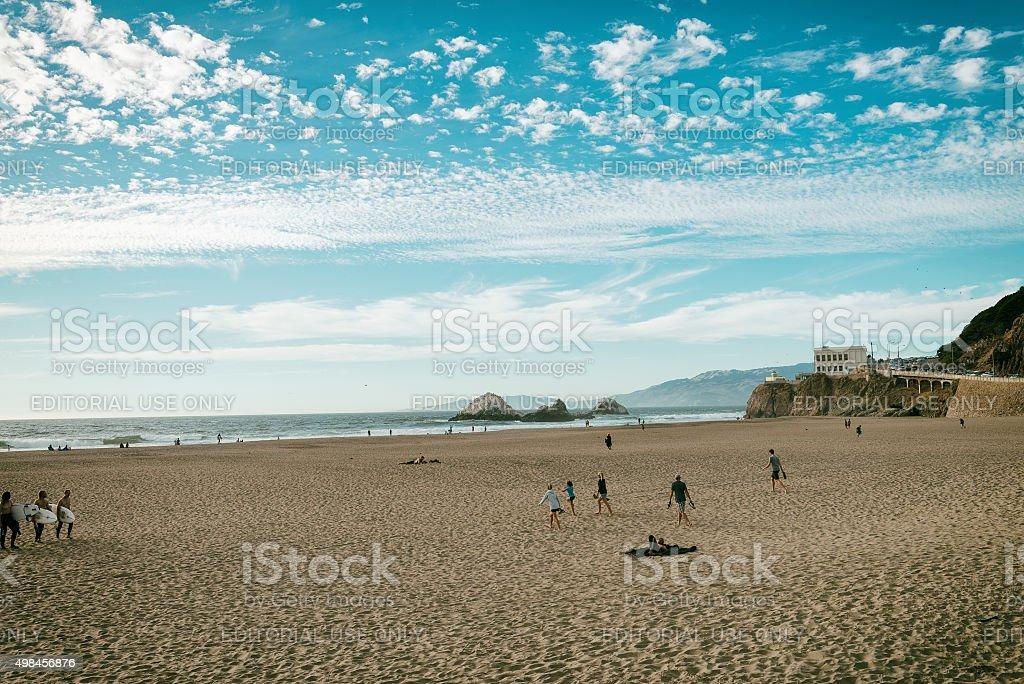 People enjoy the sand of Ocean beach stock photo