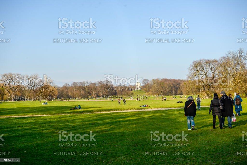 People enjoy the warm early spring weather in the Englischer Garten in Munich stock photo