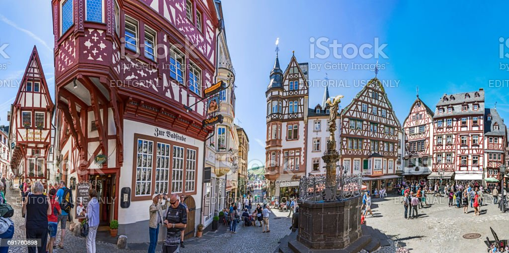 people enjoy visiting the  old historic town of Bernkastel-Kues on a summer day. stock photo