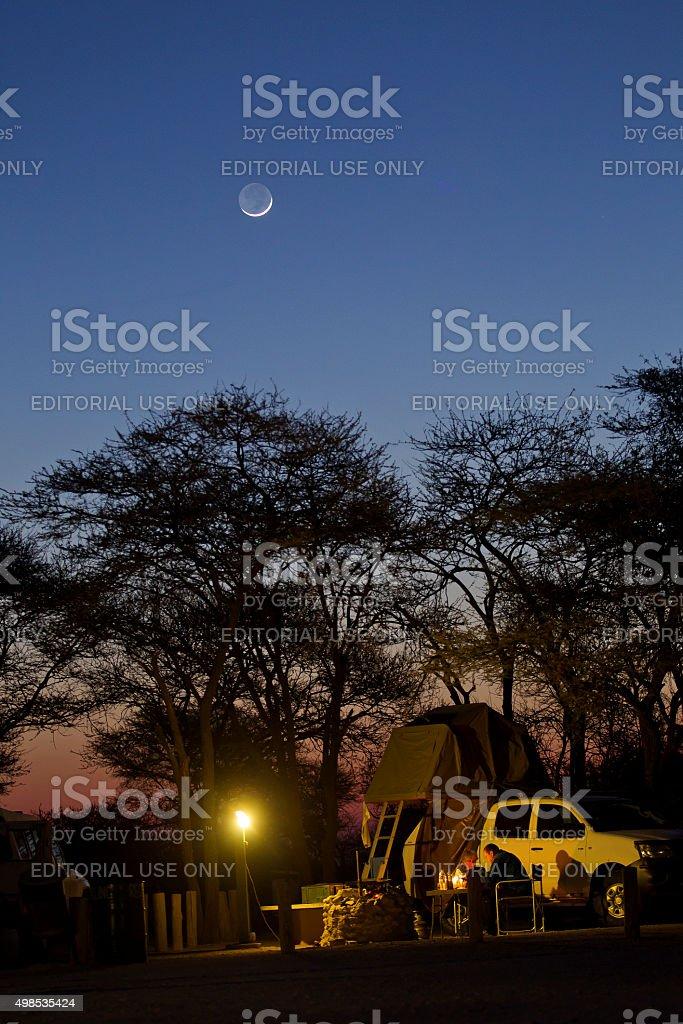 People enjoying camp at dusk at Okaukuejo, Etosha National Park stock photo