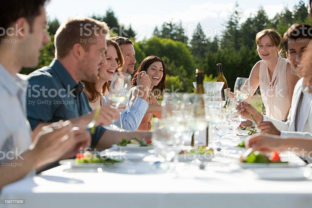 People enjoying outdoor dinner party stock photo