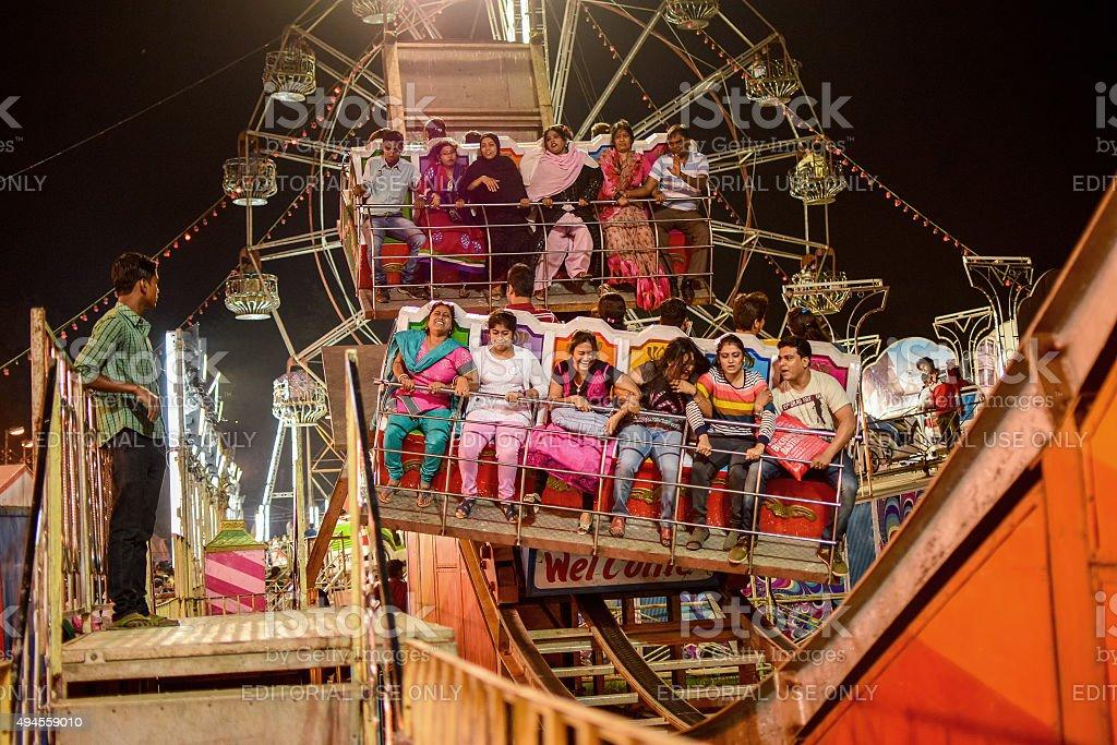 People enjoying ride on Ferris wheel at night. stock photo