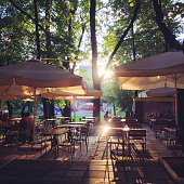 People enjoying summer evening in a park cafe