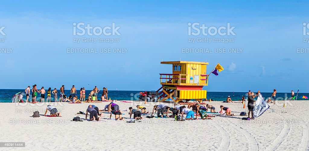 People enjoying the beach next to a colorful lifeguard tower stock photo