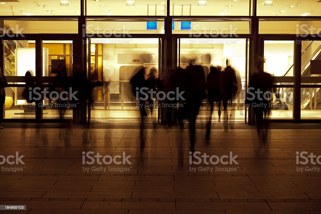 People Entering Modern Building at Evening stock photo