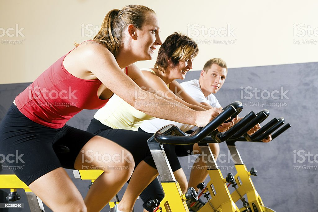 People exercising on bikes in the gym royalty-free stock photo