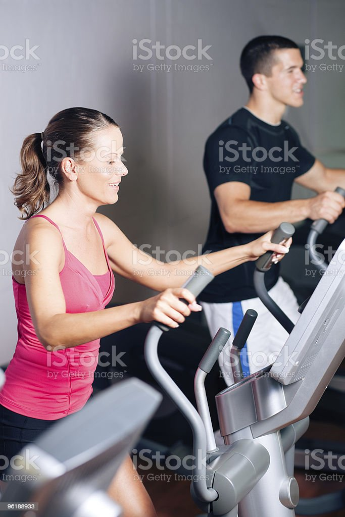 People exercising on elliptical trainer in gym royalty-free stock photo