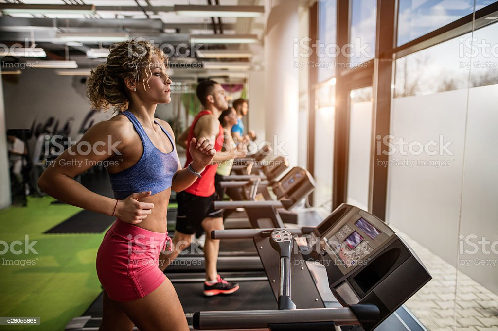 People exercising on treadmills in a gym. stock photo