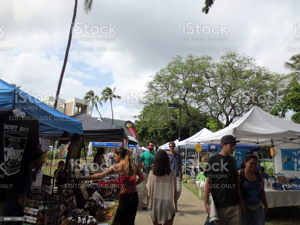People explore booths that line pathway at Earth Day stock photo