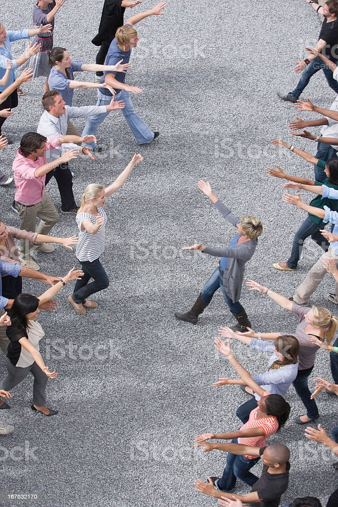 People extending arms to each other in crowd royalty-free stock photo