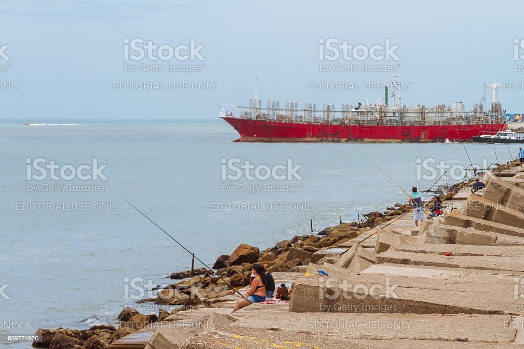 People fishing on a breakwater of the Atlantic Ocean stock photo