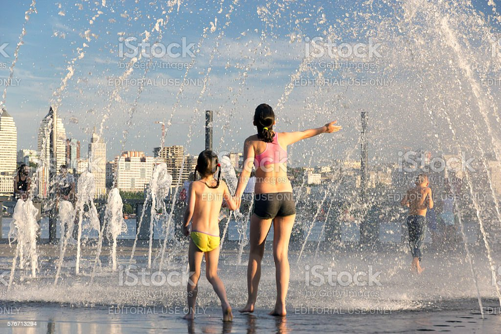 People fleeing from the heat in a city fountain stock photo