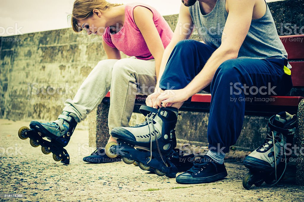 People friends putting on roller skates outdoor. stock photo