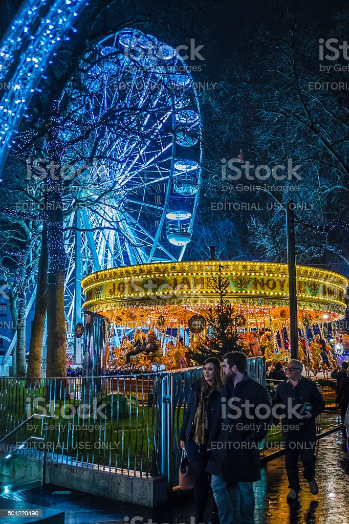 People gather around the Christmas fairground in Leicester Square, London stock photo