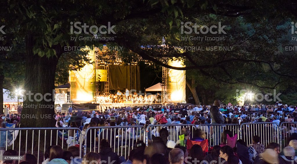 People gathered for the night time free outdoor orchestra perfor stock photo