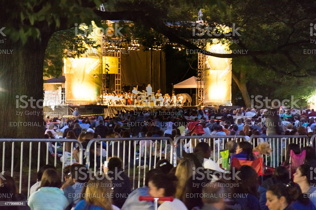 People gathered for the night time free outdoor orchestra stock photo