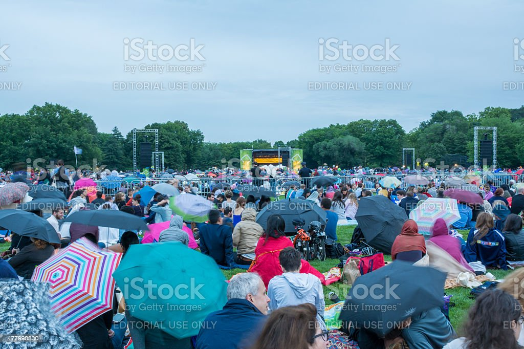 People gathered while raining for the free outdoor orchestra per stock photo