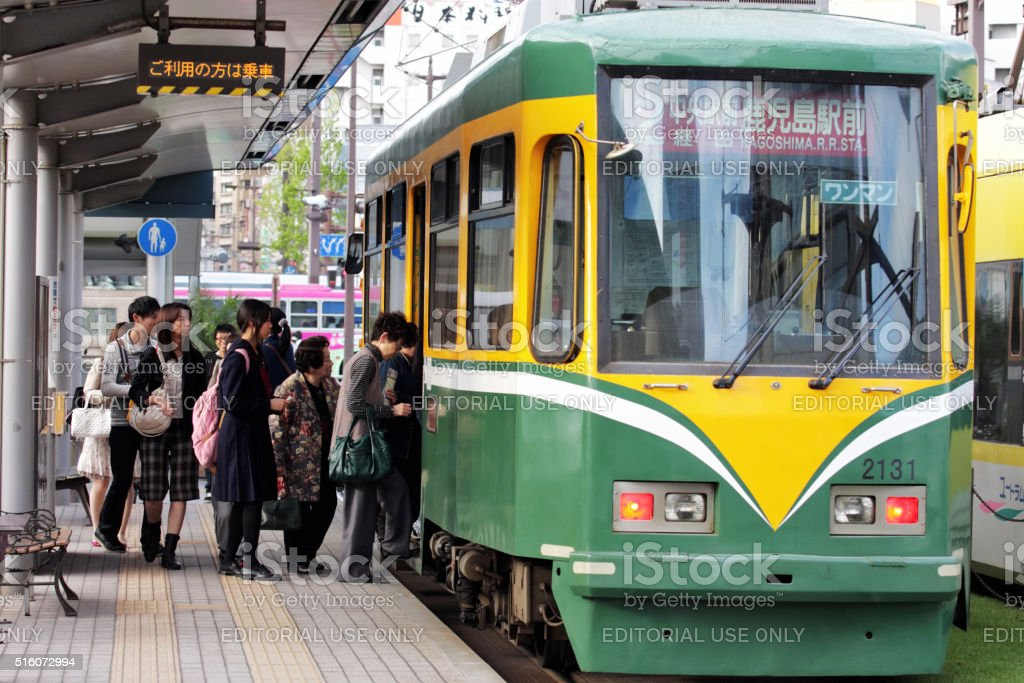 People getting into a tram in Kagoshima stock photo