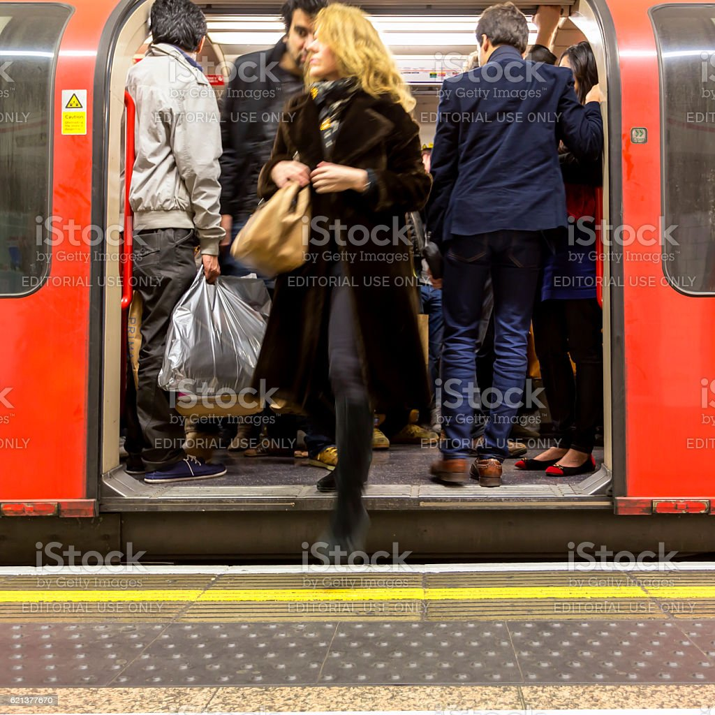 People getting off a crowded underground carriage stock photo