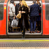 People getting off a crowded underground carriage