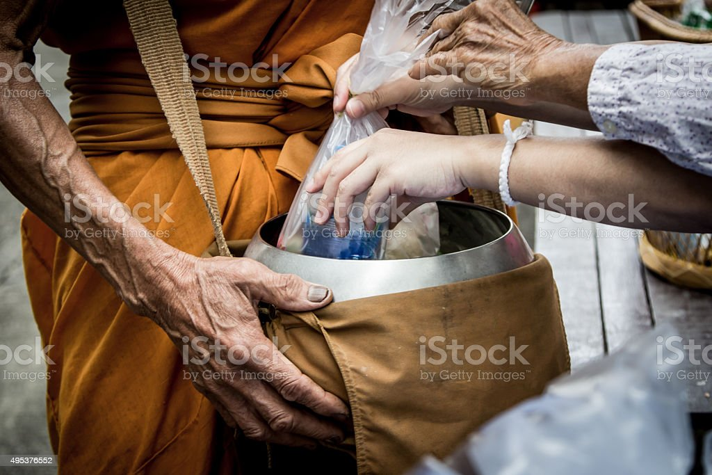 People give alms food and item offering to Buddhist monk stock photo